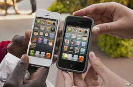 Noah Meloccaro, right, compares his older iPhone 4s to the new iPhone 5 held by Both Gatwech, outside the Apple Store in Omaha, Neb., Friday, Sept. 21, 2012 on the first day the iPhone 5 was offered for sale.