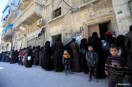 FILE - Women and children queue to receive free meals in Aleppo, Syria, Feb. 2, 2017.