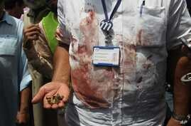 A Pakistani security official displays cartridges he collected from the scene of an attack on a bus that was bound for a Shiite community center in southern Pakistan when gunmen attacked it, killling dozens of people, Karachi, May 13, 2015.