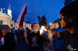 People light candles as they attend a daily protest against judicial reforms in Warsaw, Poland, July 27, 2017.