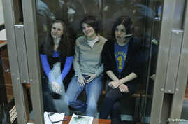 Members of the female punk band 'Pussy Riot' (L-R) Maria Alyokhina, Yekaterina Samutsevich and Nadezhda Tolokonnikova sit in a glass-walled cage before a court hearing in Moscow, October 1, 2012.