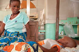 Antho watches over her son Kaba, two, who is being treated for cerebral malaria at the Tshilundu Referral Hospital in Kasai Oriental Province, DRC. Kaba is now in a coma. Antho is nine months pregnant. This is her eighth pregnancy; she had two miscar