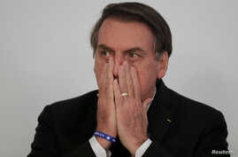 Brazil's President Jair Bolsonaro gestures during a signing ceremony for 13.2 billion reais in contracts for electricity transmission lines, at the Planalto Palace in Brasilia, Brazil, March 25, 2019.