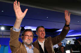 Spanish Prime Minister Mariano Rajoy and Catalan People's Party (PP) president Xavier Garcia Albiol wave as they arrive at a Catalan regional People's Party meeting in Barcelona, Nov. 12, 2017.
