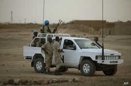FILE - In this July 28, 2013 photo, United Nations peacekeepers stand guard at a polling station, during presidential elections in Kidal, Mali.