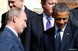 Russian President Vladimir Putin (L) walks past U.S. President Barack Obama (R) during a group photo at the G20 Summit in St. Petersburg, Sept. 6, 2013.
