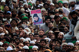 People hold the photo of police officer Mumtaz Qadri, the convicted killer of a former governor, during his funeral, in Rawalpindi, Pakistan, Tuesday, March 1, 2016.