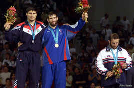 Gold medalist Sagid Mourtasaliyev (C) poses with silver medallist Islam Bairamukov at the Olympic Games in Sydney on September 30, 2000. The Russian wrestler returned his medal to protest the sport's possible exclusion from the Games.