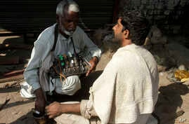 FILE - A Pakistani street barber prepare to cut a customer's hair, along a roadside in Lahore.