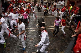 Revelers run around Nunez del Cubillo's fighting bulls on the Estafeta corner during the seventh running of the bulls at the San Fermin Festival, in Pamplona, northern Spain, Wednesday, July 13, 2016.