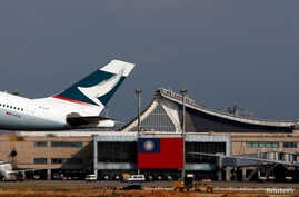FILE - Hong Kong's Cathay Pacific Airways Airbus passenger plane takes off against the backdrop of a Taiwanese flag, at Taoyuan International Airport, Taiwan, Aug. 6, 2018.
