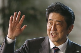 Japan's newly-named Prime Minsiter Shinzo Abe smiles as he waves at the media upon his arrival at the prime minister's official residence following his election at Parliament in Tokyo, Dec. 26, 2012.