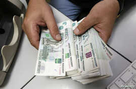 FILE - An employee counts Russian ruble bank notes at a private company's office in Krasnoyarsk, Siberia, Dec. 17, 2014. Russia's ruble strengthened on Wednesday after dramatic falls against the dollar in the previous two days but remained extremely