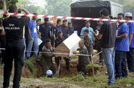 Malaysian officials provide Muslim burial to 21 human trafficking victims, believed to be Rohingya Muslim refugees, found in shallow graves in jungles bordering Thailand, in Kedah, Malaysia, June 22, 2015.