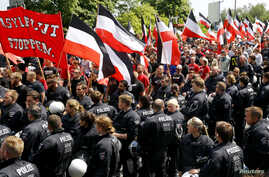 """FILE - Riot police watch as far-right supporters take part in anti-refugee rally in Dortmund, Germany, June 4, 2016. The placard in front reads """"Stop the flood of asylum seekers."""""""