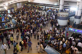 FILE - Commuters make their way through a metro station at rush hour in New Delhi, India, July 11, 2016.