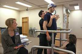Paralyzed from the torso down Jared Chinnock is seen standing after a procedure to allow him to move his legs again. (Mayo Clinic)