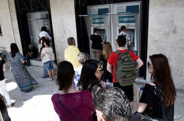 People stand in a queue to use the ATMs of a bank in the northern Greek city of Thessaloniki, June 27, 2015.