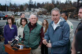 Interior Secretary Ryan Zinke, right, answers a reporters question after touring fire ravaged Paradise, Calif. with Agriculture Secretary Sonny Perdue, center, Nov. 26, 2018.