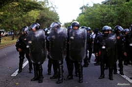 Anti-riot police observe workers participating in a roadblock at the International Airport highway as a protest against the Salvadorian government in Olocuilta, November 7, 2016. On November 8, 2016, El Salvador lost two more security officers to gan