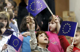FILE - Bosnian children wave European Union flags at a celebration of  European Day in the Bosnian capital Sarajevo, May 9, 2007.