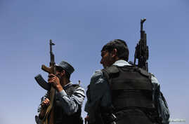 Afghan policemen keep watch as election commission workers move ballot boxes and election material to a polling station in Kabul, June 13, 2014.