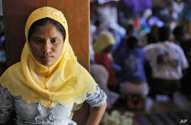 A Rohingya woman stands at a temporary shelter in Bayeun, Aceh Province, Indonesia, Monday, June 1, 2015.