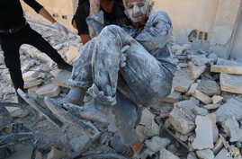 Syrian civil defense workers rescue a man from under the rubble, July 25, 2014, after a Syrian government helicopter allegedly dropped a barrel bomb on the Sakhour eastern neighborhood, in the northern city of Aleppo.