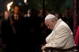 Pope Francis bows his heads and closes his eyes during the Via Crucis (Way of the Cross) torchlight procession in Rome, April 18, 2014.