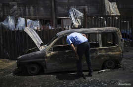 An Israeli man looks at a burnt car parked beside a paint factory in the southern town of Sderot, Israel, June 29, 2014.