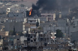 A fire burns in the Syrian city of Kobani, seen from a hilltop outside Suruc, on the Turkey-Syria border, Nov.13, 2014.