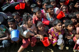 Rohingya Muslim children, who crossed over from Myanmar into Bangladesh, wait squashed against each other to receive food handouts distributed to children and women by a Turkish aid agency at the Thaingkhali refugee camp in Ukhiya, Bangladesh, Nov. 1