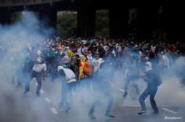 Demonstrators are seen amidst tear gas fired by security forces during an opposition rally in Caracas, Venezuela April 6, 2017.