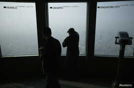 """A woman looks at central Seoul shrouded in heavy haze at an observation platform at """"N Seoul Tower"""" located atop Mt. Namsan in central Seoul, Feb. 27, 2014."""