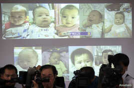 FILE - Surrogate babies that Thai police suspect were fathered by a Japanese businessman who has fled from Thailand are shown on a screen during a news conference at the headquarters of the Royal Thai Police in Bangkok.