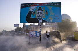 Afghan man shields himself from dust behind a billboard of then-incumbent presidential candidate Hamid Karzai, Kabul, August 13, 2009.