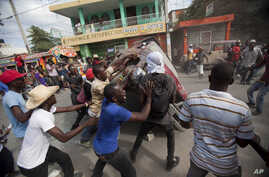 Demonstrators flip a car to block off a street during a protest demanding the resignation of President Michel Martelly in Port-au-Prince, Haiti, Jan. 11, 2015.