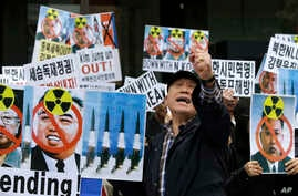 South Korean protesters holdr pictures of North Korean leader Kim Jong Un,  national founder the late Kim Il Sung and late leader Kim Jong Il during a rally against recent missile launches and provocative acts in Seoul, South Korea, April 15, 2014.