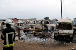 Burned minivans are seen outside the main prison in Kinshasa, Congo, Wednesday May 17, 2017. Christian sect members stormed a prison in Congo's capital Wednesday, freeing the leader of their movement and 50 others, Congo's justice minister said.