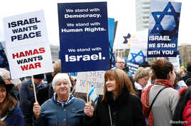 """People hold placards during the """"Rally for Equal Rights at the United Nations (protesting Anti-Israeli bias)"""" aside of the Human Rights Council at the United Nations in Geneva, Switzerland, March 18, 2019."""