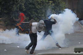 An anti-government protester throws tear gas canister fired by riot police during clashes after the funeral procession of Ali Abbas and Ahmed Al Mesjen who died when their car exploded in the village of Maqsha west of Manama, April 22, 2014.