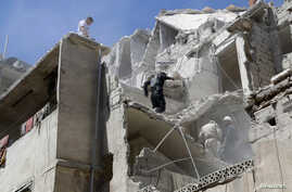 Residents look for survivors among the debris and damage after what activists said was shelling from forces loyal to Syria's President Bashar al-Assad at Al-Kallaseh in Aleppo, Syria, May 17, 2014.