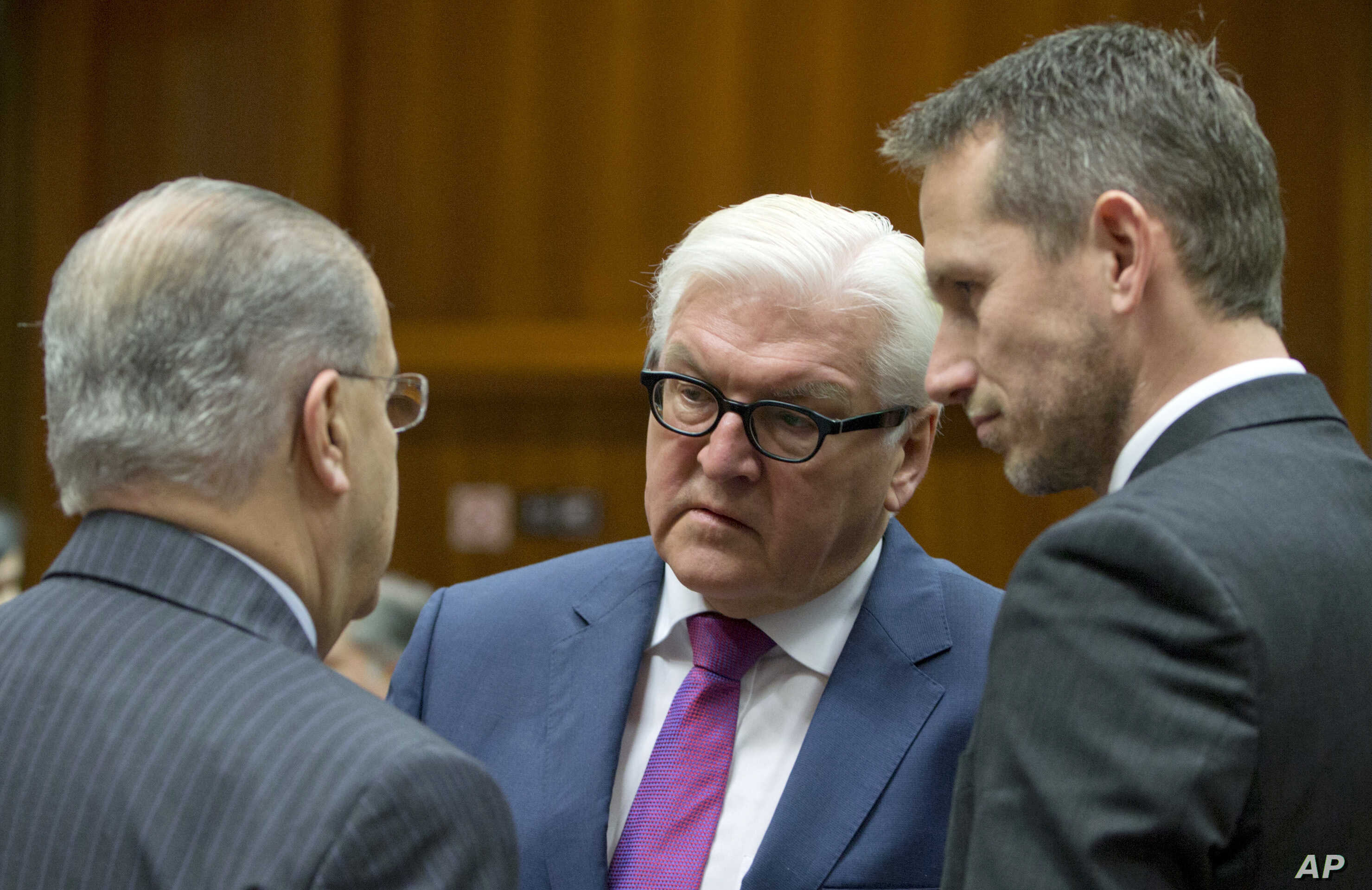 German Foreign Minister Frank-Walter Steinmeier, center, speaks with Cypriot Foreign Minister Ioannis Kasoulides, left, and Danish Foreign Minister Kristian Jensen, right, during a meeting of EU foreign ministers at the EU Council building in Brussel