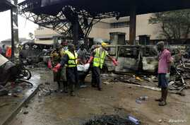 Rescue workers carry a body from the remains of a fuel station that exploded overnight in Accra, Ghana, June 4, 2015.