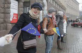 Demonstrators make a symbolic human chain as a symbol of integration with the European Union during a rally in the center of Kiev, Ukraine, Nov. 29, 2013.