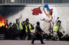 "A woman passes by a mural by street artist PBOY depicting Yellow Vest (gilets jaunes) protesters inspired by a painting by Eugene Delacroix, ""La Liberte guidant le Peuple"" (Liberty Leading the People), in Paris, Jan. 10, 2019."
