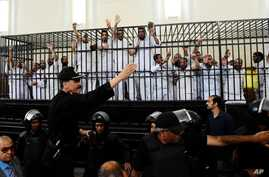 Supporters of the Muslim Brotherhood and other Islamists gesture from the defendants cage as they receive sentences after they were convicted of murder, rioting, and violence in a mass trial in Alexandria, Egypt, May 19, 2014.