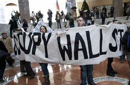 Protesters affiliated with the Occupy Wall Street movement hold up a sign in the center of Winter Garden Atrium in Three World Financial Center, New York, New York, December 12, 2011.