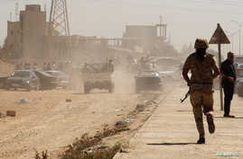 Members of the Libyan National Army make their way to the gates of pro-government Rafalla al-Sihati brigade after demonstrators attacked the brigade's base in Benghazi city, September 22, 2012.
