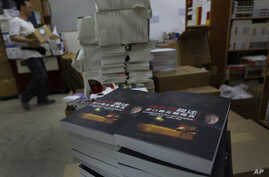 """FILE - A worker walks past a stack of books by former Beijing mayor Chen Xitong, titled """"Conversation with Chen Xitong,"""" at a publisher's warehouse, one day before the launch of the book in Hong Kong."""